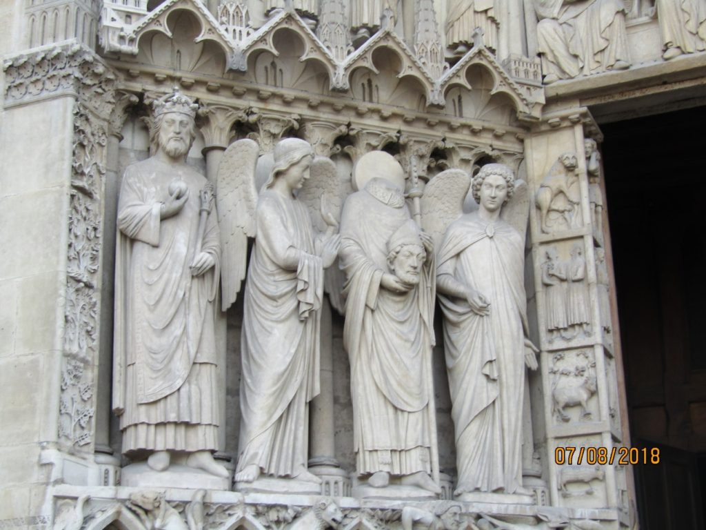Notre Dame Cathedral - Saint Denis holding his head and two angel- photo Lysandra Furstenberg