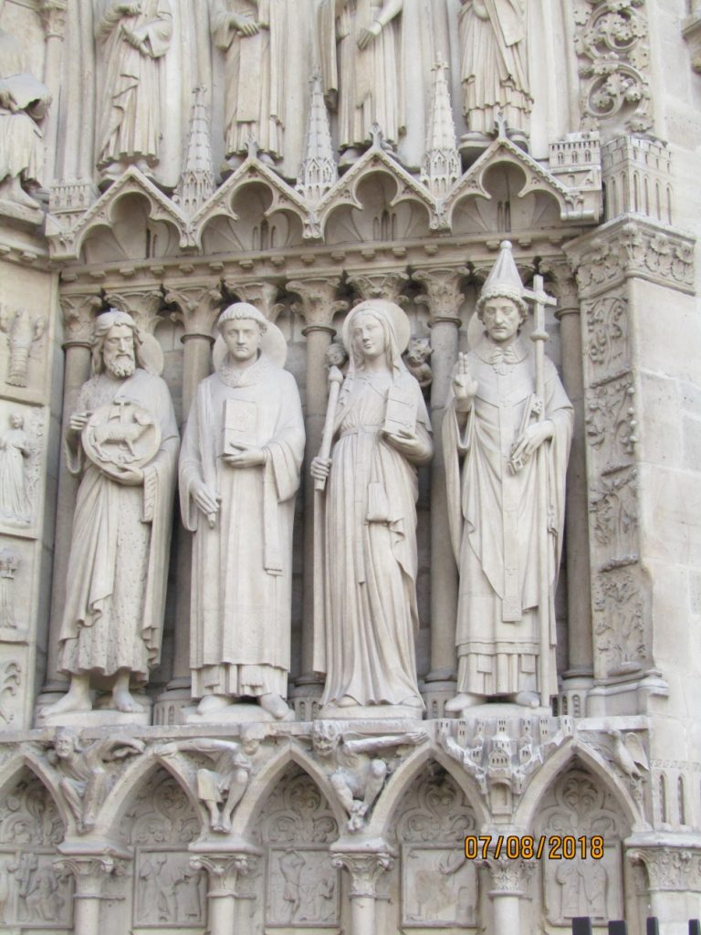 Notre Dame Cathedral - Statues of Saint John the Baptist, Saint Stephen, Saint Genevieve, Pope Saint Sylvester on Portail de la Vierge - photo by Lysandra Furstenberg.jpg