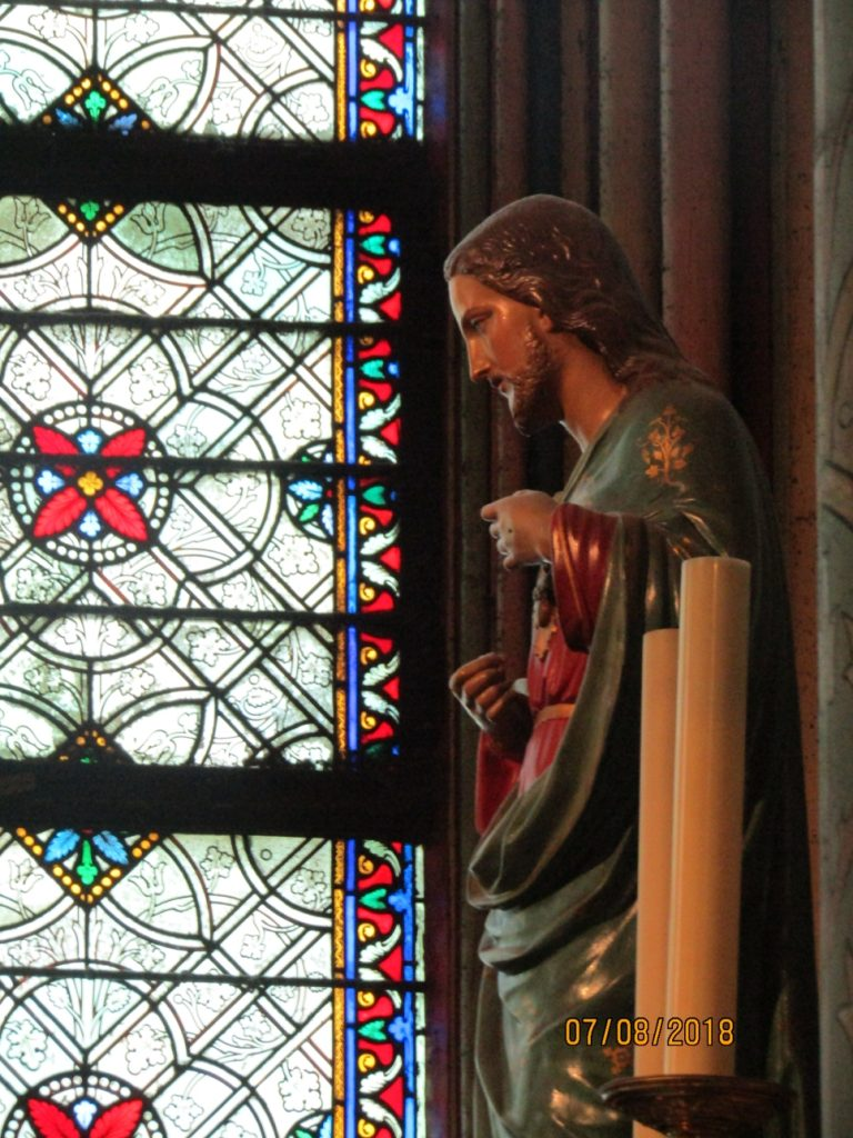 Notre Dame Cathedral interior = Statue and stained glass window - photo by Lysandra Furstenberg