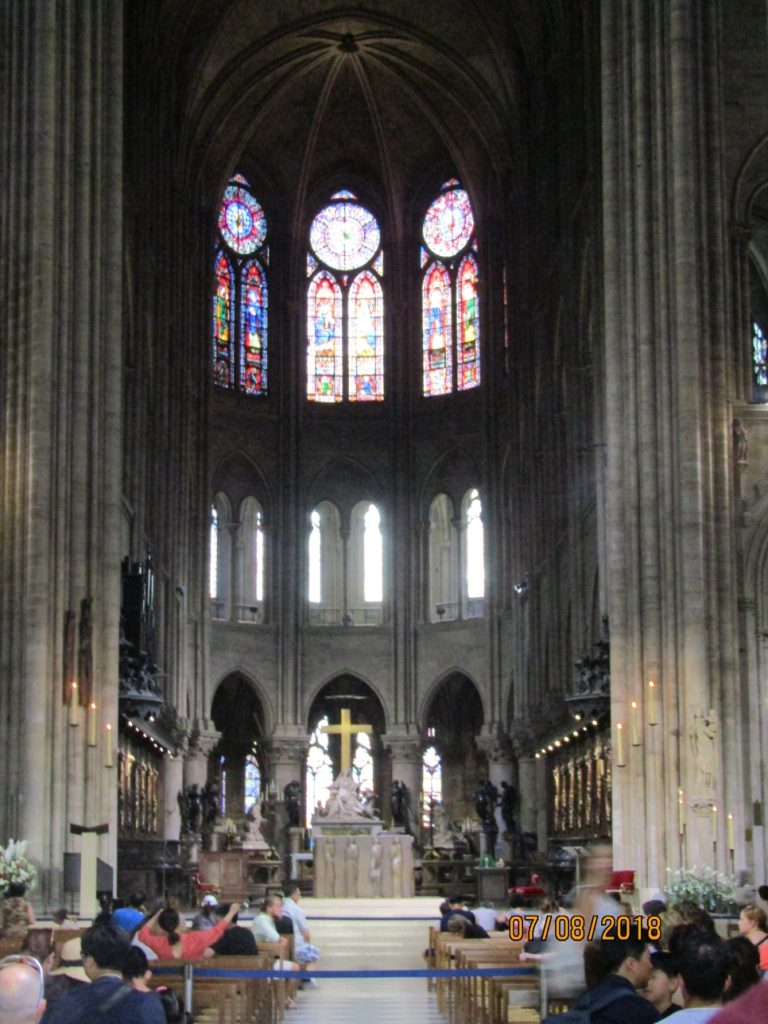 solemn interior of the Notre Dame Cathedral in Paris with stained glass windows and altar with cross and crucifix - photo by Lysandra Furstenberg