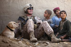 Happiness can be found anywhere. Sometimes you just need to search harder or ask for someone to help you discover it. A US Marine, his MWD, military working dog and Afghan boys.