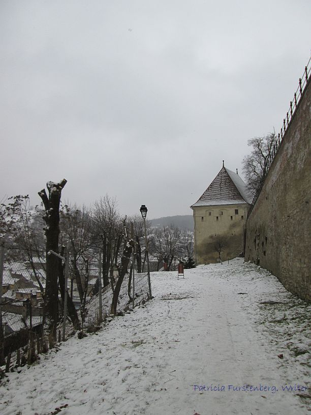 A snow covered path outside the walls of Medieval Sighisoara - marvel medieval towers fortress