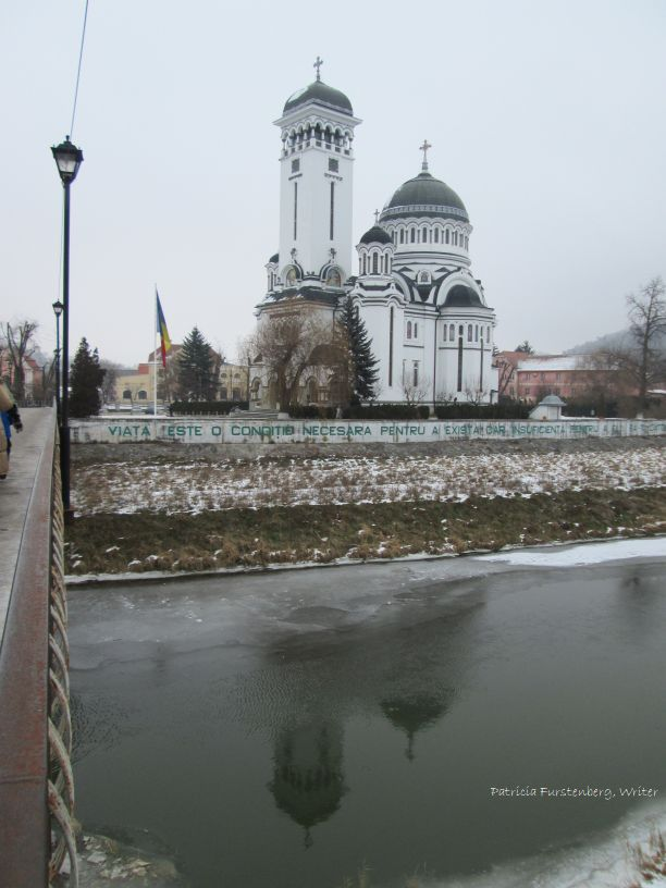 the Orthodox Cathedral reflected in a frozen Tarnava Mare river