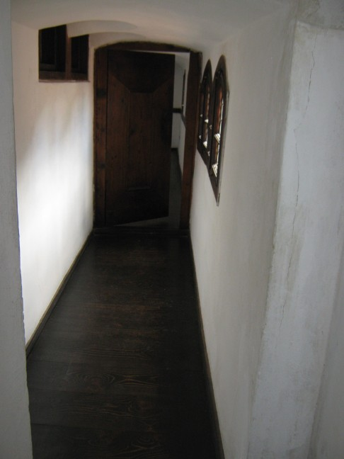 Lovely wood floors and a wooden door near twin windows at Bran Castle