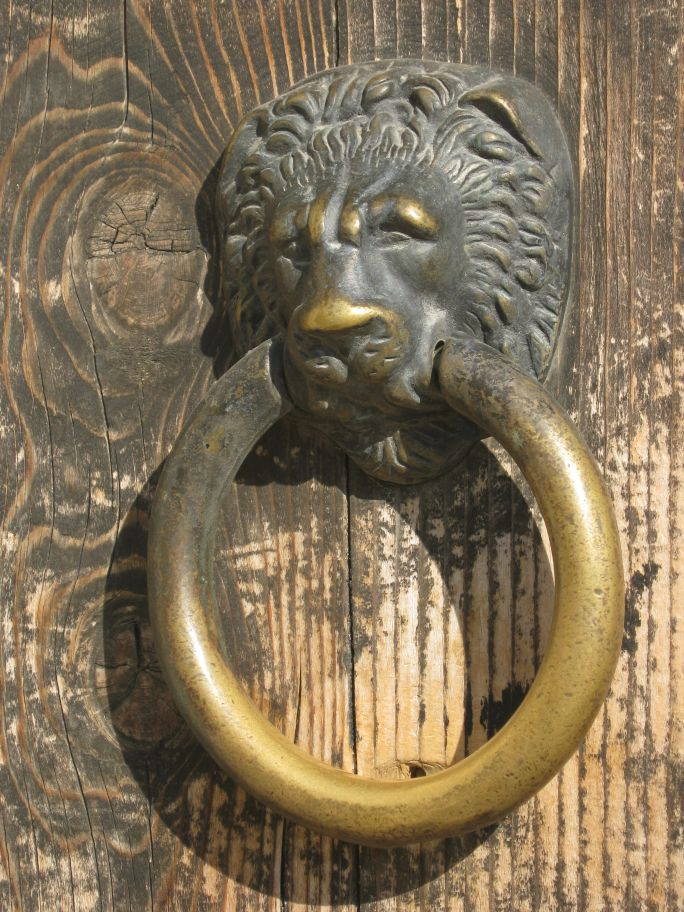 Travel to Râșnov Fortress, Romania, Rasnov fortress lion brass door knocker on a medieval door