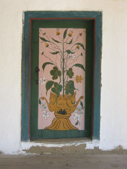 A door with a painting in shades of green and a dark teal door frame, Village Museum